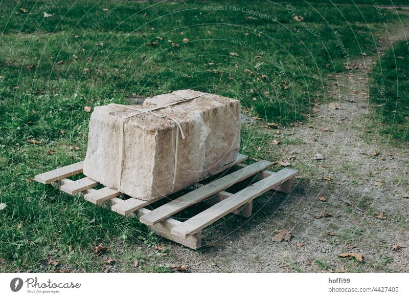schwerer Steinquader verschnürt auf einer Palette Bildhauerei Anlieferung Verpackung transport Paket Versand Spedition Transport Quader Quaderstein Sandstein