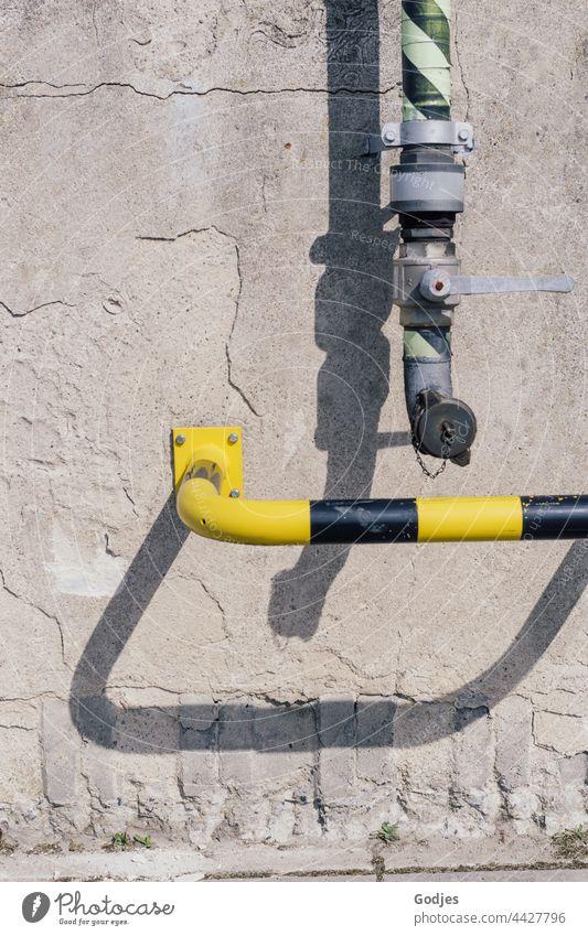 Rohr einer Pumpanlage und Sicherheitsbügel in gelb schwarz an einer Betonwand. Rohrleitung Menschenleer Außenaufnahme Röhren Wand Farbfoto Mauer Wasserrohr