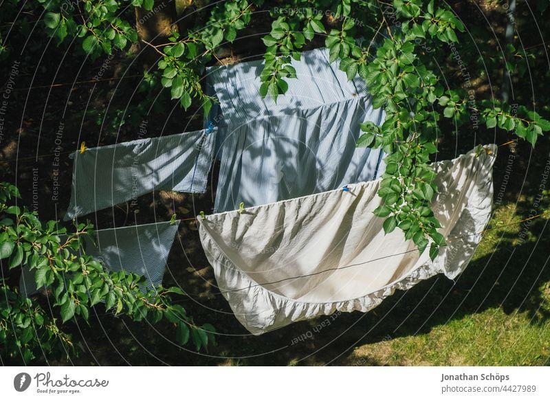 Bettwäsche beim Trocknen auf der Wäscheleine draußen im Garten wäsche aufhängen Wäsche trocknen Wind Hof Hinterhof Wiese Baum Zweige Äste Leine Bettbezug