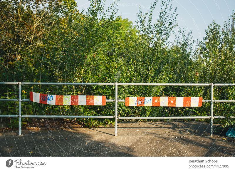 Sackgasse Straßenende Zaun Absperrung vor Natur Fußweg rot Weiß Geländer Schluss Ende Büsche Bäume Umwelt Stopp Außenaufnahme Sicherheit Barriere rot-weiß