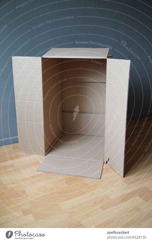 aufrecht stehender leerer Karton im Zimmer Verpackung Paket Verpackungsmaterial Versand Umzug (Wohnungswechsel) auspacken zimmer fußboden Kiste Schachtel