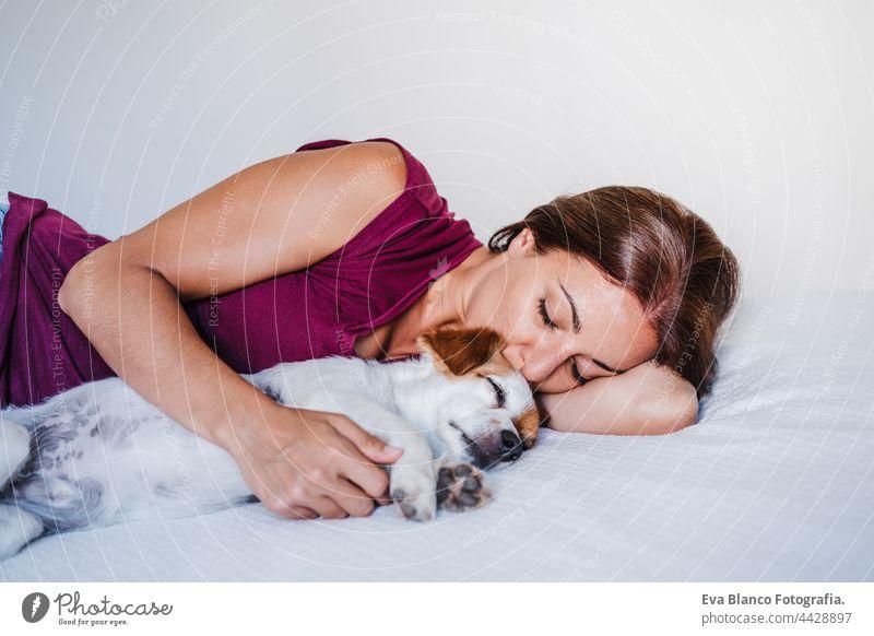 junge kaukasische Frau zu Hause ruht auf dem Bett mit niedlichen Jack Russell Hund. Haustiere, Liebe und Entspannung jack russell schlafen sich[Akk] entspannen