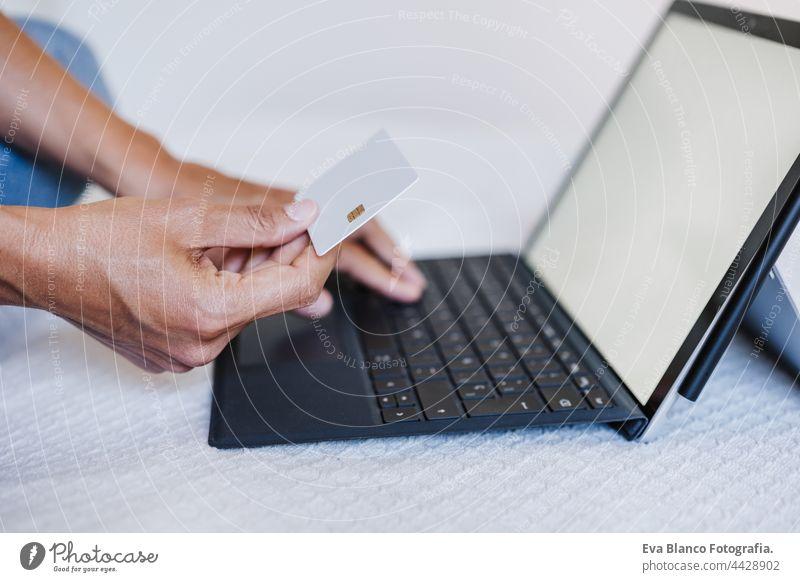 Nahaufnahme einer nicht erkennbaren Frau beim Online-Shopping mit Kreditkarte und Laptop. Technologie und Business-Konzept Kreditwagen abschließen unkenntlich