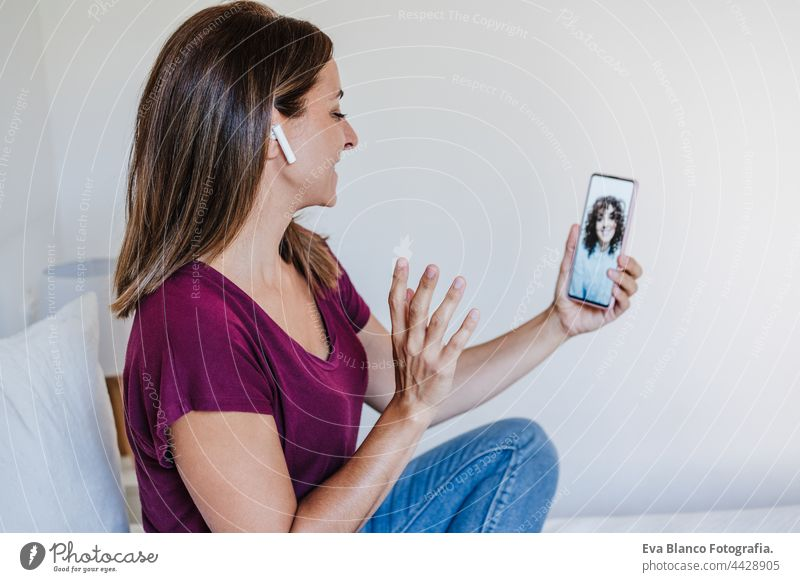 glückliche kaukasische Frau zu Hause tun Videoanruf mit Freunden auf dem Handy. Heimbüro und Freundschaft heimwärts Bett Kaukasier 30s Glück Lächeln schön jung