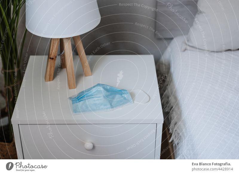 blaue Schutzmaske auf dem Nachttisch im Schlafzimmer zu Hause. Niemand. Corona-Virus und Pandemie-Konzept heimwärts niemand Gesichtsmaske im Innenbereich Raum