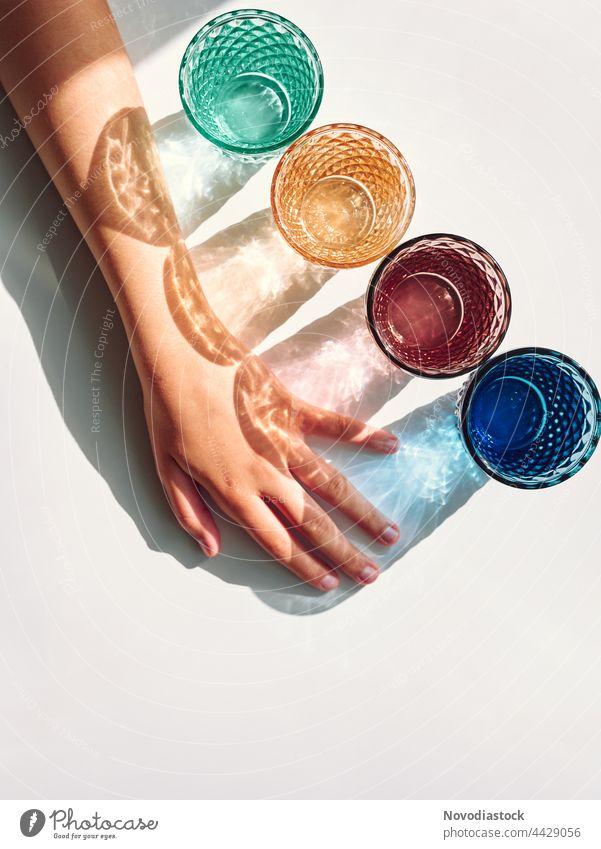 Bunte Brille mit Schatten und einem Mädchenarm isoliert auf einem weißen Hintergrund Glas trinken Getränk Farbfoto Innenaufnahme Trinkwasser Tag Wasser
