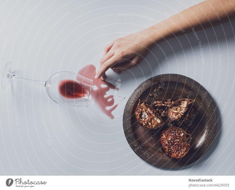 Ein Arm, ein Teller mit Granatäpfeln und ein Glas Wein auf einem Tisch verschüttet Hand Finger Frau Mensch Farbfoto Innenaufnahme Arme Granatapfel Schatten