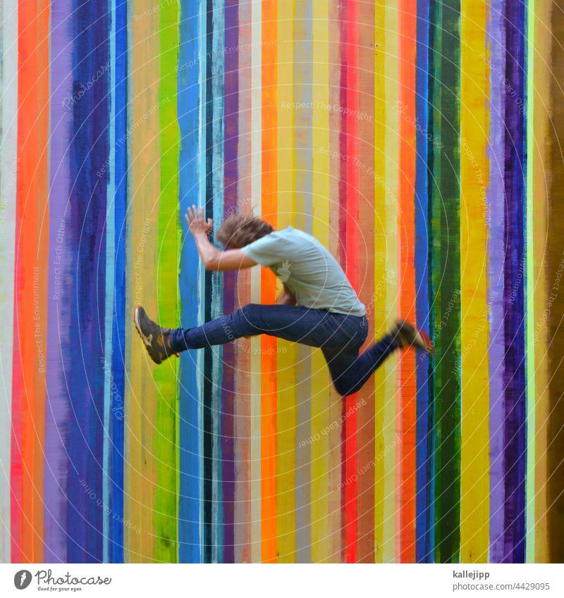 farbenfroh Farbe Farbstreifen Farbfoto springen Mann Mensch hüpfen bunt Regenbogen Streifen sportlich Sport Freude Außenaufnahme Jugendliche Spielen Bewegung