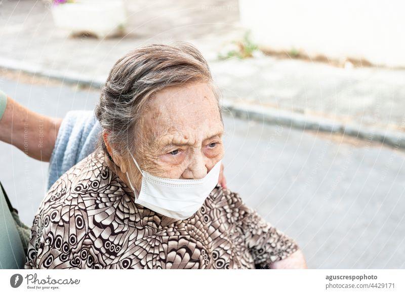 Nahaufnahme einer achtzigjährigen Frau, die in einem Rollstuhl die Straße hinuntergeht, mit Blick nach vorn in einem gemusterten Hemd, die eine Schutzmaske trägt.