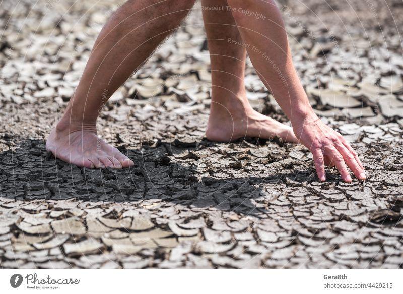 nackte Füße einer Person auf trockenem Boden ohne Pflanzen in Nahaufnahme Hintergrund schlechte Ökologie Barfuß Klima Risse Krise wüst Desaster Dürre trocknen