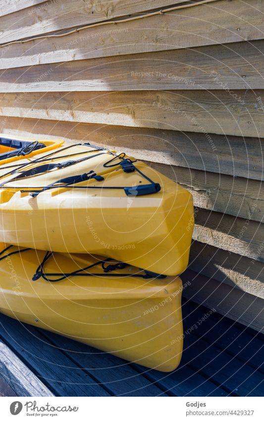 zwei gelbe Kajaks gestapelt neben einer Holzwand Plastik Farbfoto Außenaufnahme Wasser Sport Wassersport Menschenleer Tag Ferien & Urlaub & Reisen