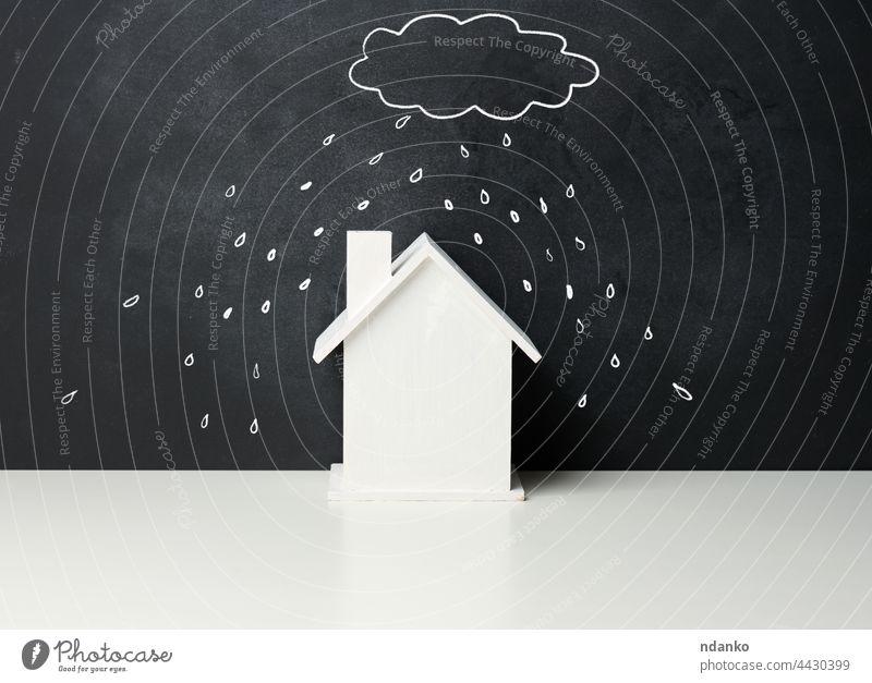 Holzhaus und eine gezeichnete Wolke mit Regen mit weißer Kreide auf einer schwarzen Kreidetafel. Immobilien Versicherung Konzept hölzern Problematik Unwetter
