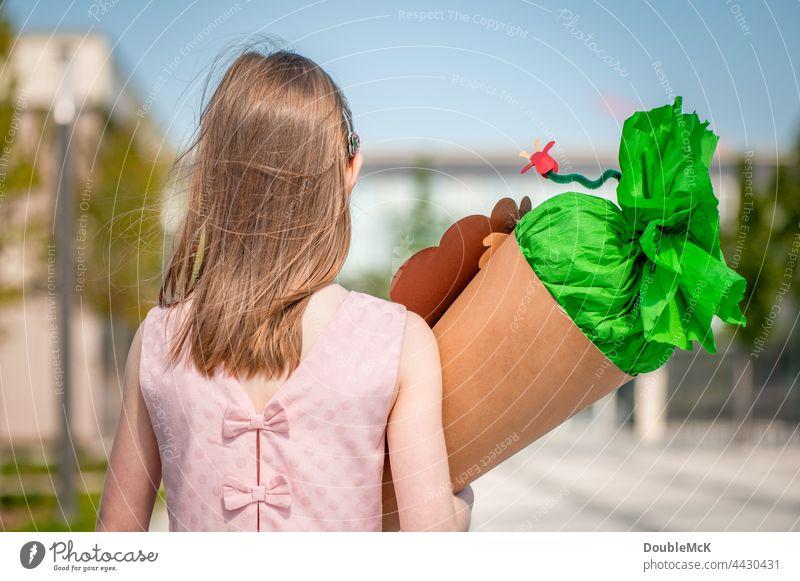 Ein Mädchen steht vor der Schule mit einer Schultüte auf dem Arm Zuckertüte Einschulung Kind Farbfoto Kindheit Bildung lernen Schulkind Schüler schülerin Mensch