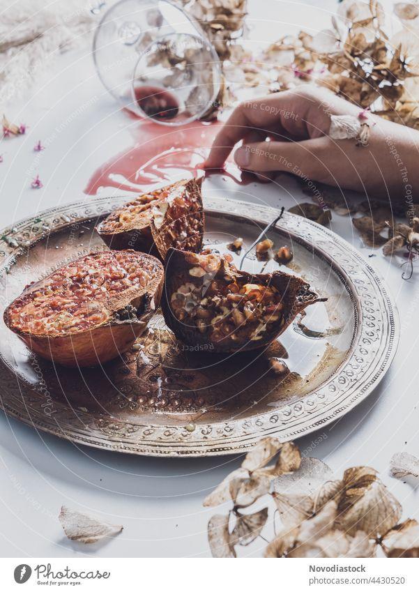 Granatäpfel auf einem Teller aus Stahl, in der einen Hand ein Glas auf dem Tisch, Stillleben Geschirr Farbfoto Innenaufnahme Lebensmittel Granatapfel