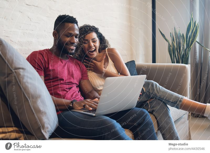 Ein Paar benutzt einen Laptop, während es zu Hause auf der Couch sitzt. heimwärts Mann Frau zwei Lifestyle Zusammensein Sofa Partnerschaft Freund Freundin