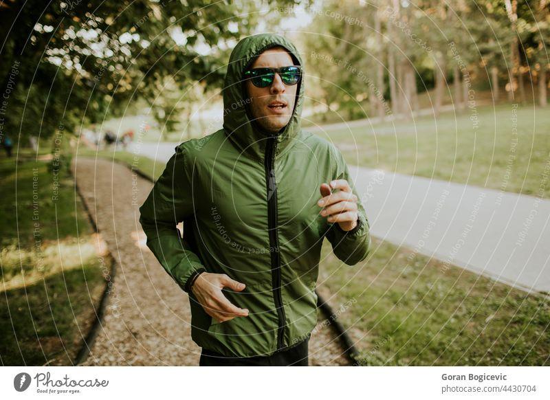 Sportlicher junger Mann, der in einem sonnigen grünen Park trainiert Aktion aktiv Aktivität Erwachsener Athlet sportlich Kaukasier Ausdauer Übung passen Fitness