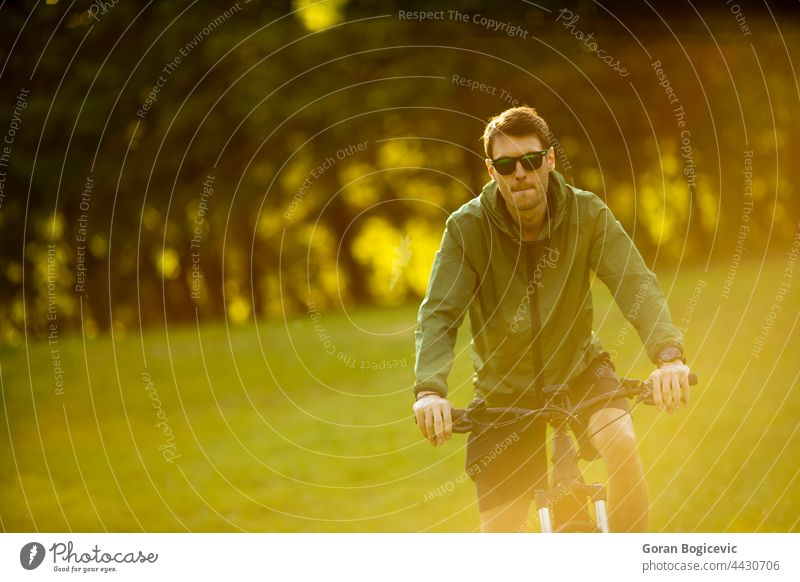 Junger Mann fährt E-Bike im Park aktiv Batterie Fahrrad Biker Radfahren schwarz Zyklus Radfahrer ebike Öko ökologisch Ökologie elektrisch Elektro Energie Motor