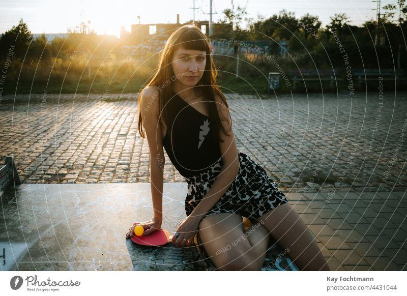stilvolle kaukasische Frau lehnt sich an eine Tischtennisplatte aktiver Lebensstil schön Freizeitkleidung kaukasische Ethnizität Abend Hüfte Hipster menschlich