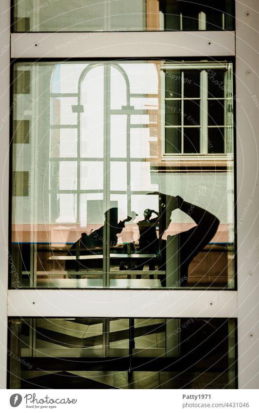 Menschliche Silhouetten vor einer geometrischen Fassade reflektieren in einer Glasscheibe | Ordnung im Chaos Fenster Reflektion Spiegelung