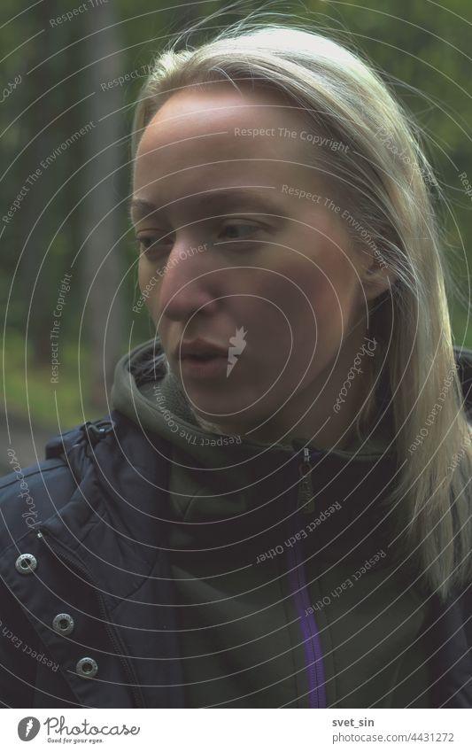 Porträt einer blonden jungen Frau im Halbprofil im Freien vor einem Waldhintergrund. Mädchen natürlich allein Lifestyle Gesicht Person Nahaufnahme Auge