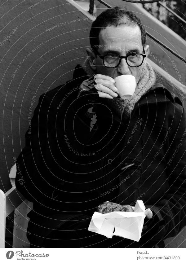 Kalter Kaffee Mann Brille kalt sitzen Winter Schal Bank Jacke Fahrradhandschuhe Croissant trinken Pause Corona Lockdown Sitzbank