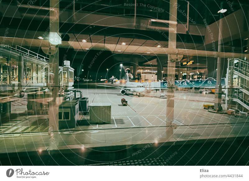 Blick aus dem Fenster am Flughafen auf ein Flugzeug bei der Abfertigung Reise fliegen nachts Spiegelung Fernweh verreisen Luftverkehr