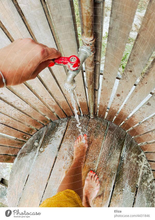 Eine Frau wäscht sich an einer Stranddusche den Sand von den Füßen waschen Urlaub Dusche Dusche (Installation) Wasser draußen strandurlaub Wassertropfen Beine