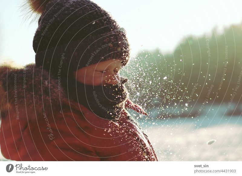 Schneeflocken glitzern im Sonnenlicht in der Luft vor dem Gesicht eines Kindes, das seine Augen geschlossen hat. Ein Junge in Winterkleidung spielt an einem frostigen, sonnigen Wintertag im Freien mit Schnee.