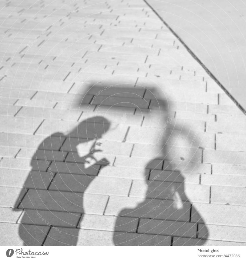 Schattenspielerei 2 Personen Kontrast Mensch Smartphone Zusammen Straße Stadt Pflaster Boden Außenaufnahme Menschen Silhouette gemeinsam Spaziergang gehen