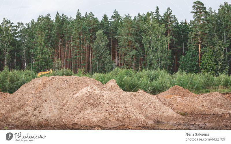 Industrielle Sandgrube. Sandgrube. Bauindustrie. Sandhügel gegen grünen Wald und bewölkten Himmel Aktivität Hintergrund blau Gebäude Planierraupe Business