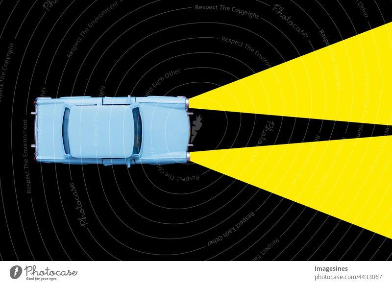 Hellblaues Retro Spielzeugauto und Xenonlampen-Scheinwerferkonzept auf schwarzem Hintergrund. Mieten Sie ein Auto, Reiseunfall. minimales Konzept abstrakt