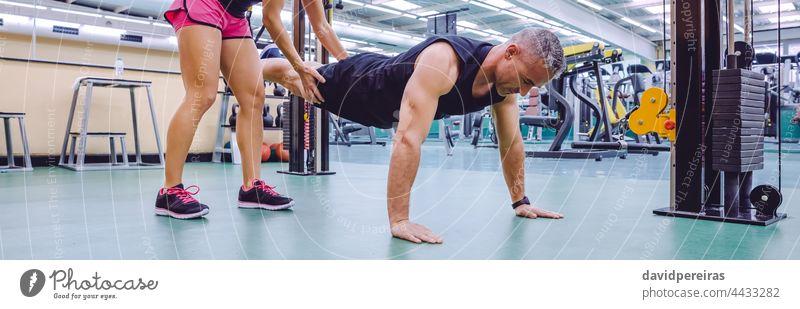 Weiblicher Trainer unterrichtet einen Mann beim Suspensions-Training panoramisch Frau Trainerin Lehre Hilfe Fitnessstudio trx Netz Ausbilderin Personal Kraft