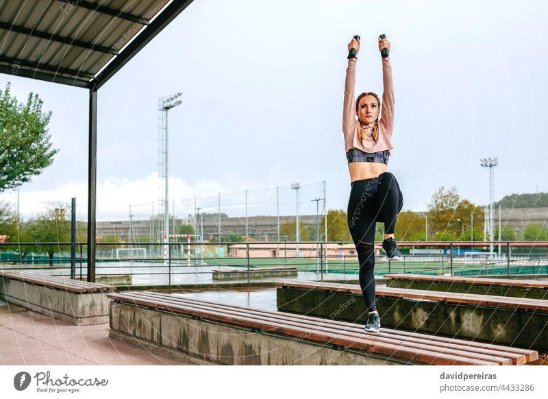 Junge Frau trainiert mit Hanteln im Freien Training Kurzhantel Arme hoch strecken Bein Knie Textfreiraum Kraft Übung Aufwärmen jung auf einer Bank Gesundheit