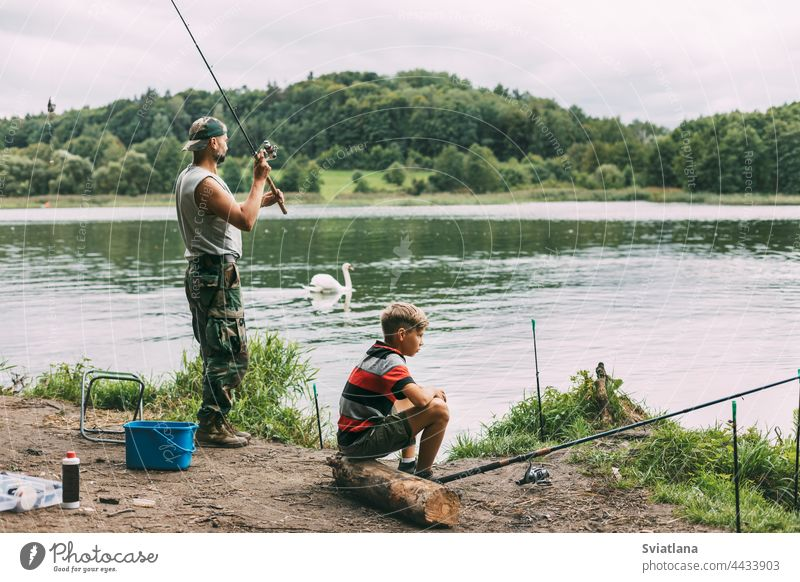 Ein junger Mann bringt seinen Kindern während eines Familienurlaubs auf einem Campingplatz das Angeln bei. Hobbys, Urlaub, Wochenenden, Angeln Fischen