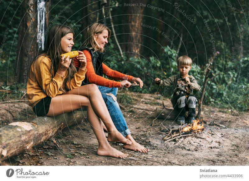 Eine junge Mutter sitzt mit ihren Kindern bei einem gemeinsamen Urlaub am Lagerfeuer, ein Mädchen isst Mais Camping Mama Wochenende Wanderung Tochter Sohn
