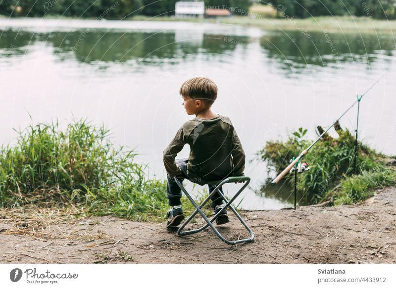Der Junge sitzt auf einem Klappstuhl am Ufer eines Sees oder Flusses. Erholung, Wochenenden, Tourismus. Rückansicht Stuhl Kind Sommer Lifestyle Freizeit