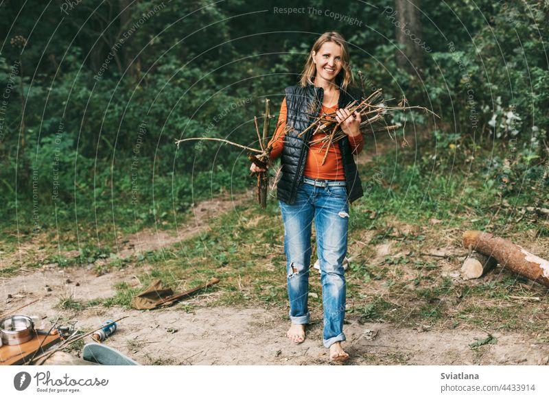 Ein Touristenmädchen sammelt in der Natur Brennholz für ein Feuer. Eine Frau in Großaufnahme. Das Konzept von Reisen und Abenteuer Camping Freudenfeuer reisen