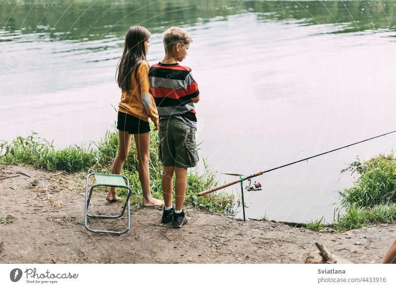 Ein Bruder und eine Schwester stehen am Flussufer und angeln während eines Familienurlaubs auf einem Campingplatz. Gemeinsame Zeit, Familienurlaub Fischen Junge