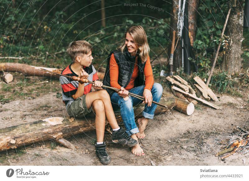 Eine Mutter und ihr jugendlicher Sohn sitzen auf einem Baum auf einem Campingplatz und probieren gegrillte Würstchen, die auf einem Feuer zubereitet wurden