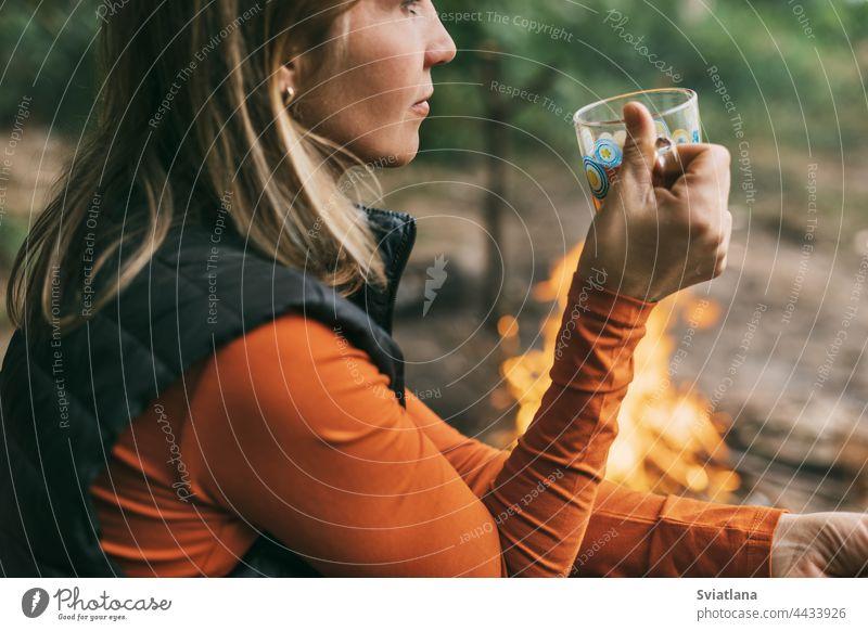 Nahaufnahme einer erwachsenen Frau, die mit einer Tasse Tee am Feuer sitzt und sich im Wald entspannt Camping trinken Sitzen jung Natur Tourist Abenteuer Urlaub