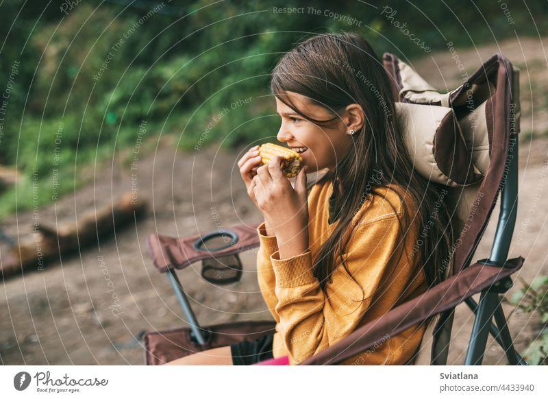 Ein junges Mädchen in einem leuchtend gelben Pullover sitzt in einem Campingstuhl am Ufer des Sees und isst Mais Lager Stuhl Sitzen essen Frau Natur Menschen