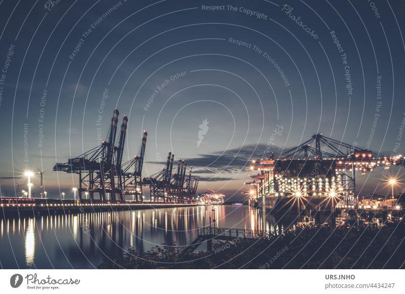 typische Hafenszene in der Dämmerung mit beleuchteten Containerschiffen und hoch in den Himmel ragenden Hafenkränen Schiff Industrie Transport Fracht Frachter