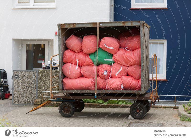 Wäschewagen vor einer Wohunterkunft anhänger aussenaufnahme farbaufnahme fahrzeug containerwagen landung mobil niemand service textilservice wäsche wäscherei