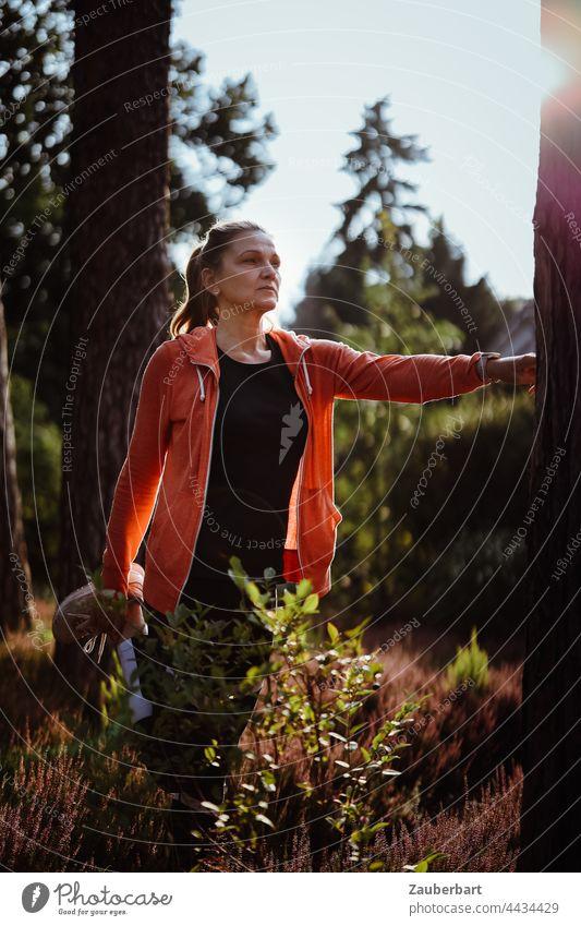Sportliche Frau mit Pferdeschwanz beim Stretching in der Heide stretching schön sportlich Sonne orange Gegenlicht joggen laufen Joggen Fitness Lifestyle