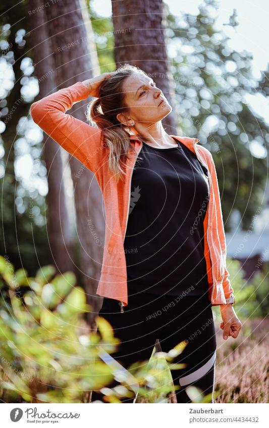 Sportliche Frau mit Pferdeschwanz beim Stretching unter Bäumen stretching Dehnen schön Dehnübungen sportlich Heide Sonne orange Gegenlicht joggen laufen Joggen