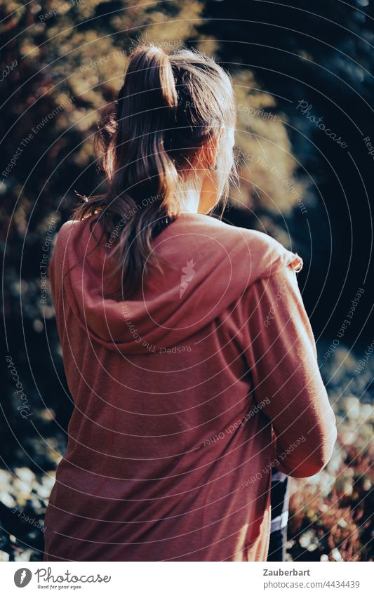Sportliche Frau mit Pferdeschwanz und Hoodie beim Stretching stretching Dehnen schön Dehnübungen sportlich Heide Sonne orange Gegenlicht joggen laufen Fitness