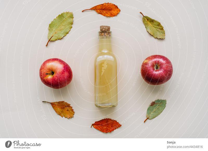 Naturtrüber Apfelsaft in einer Glasflasche und Herbstblätter Apelsaft frisch umrahmt Design Draufsicht Getränk Saft Gesunde Ernährung Diät