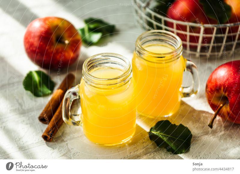 Frischer Apfelsaft in zwei Gläser und rote Äpfel auf einem weißen Tisch Saft Glas Getränk Erfrischungsgetränk Frühstück lecker trinken Innenaufnahme Limonade