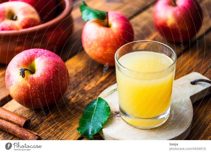 Frischer Apfelsaft im Glas und rote Äpfel auf einem Holztisch Trinkglas Herbst frisch lecker Bioprodukte Innenaufnahme Gesunde Ernährung Gesundheit natürlich