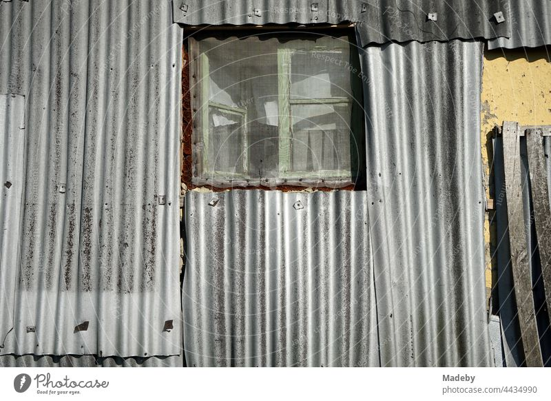 Haltes Holzfenster mit Insektengitter in alter silbergrau Wellblechfassade eines Wohnhaus im Sommer bei Sonnenschein im Dorf Maksudiye bei Adapazari in der Provinz Sakarya in der Türkei